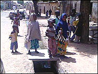 Children standing over an open sewer