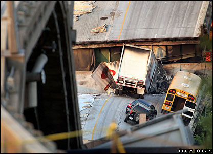 Cars rest on a section of the I-35W highway bridge a day after it collapsed