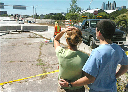 Two onlookers survey the damaged bridge in Minneapolis