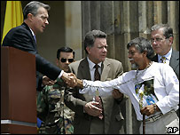 President Alvaro Uribe (l) shakes hands with Gustavo Moncayo, still wearing chains symbolising the plight of hostages held by Farc - 2/08/2007