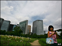 A girl stands under storm clouds in Tokyo on 2 August 2007