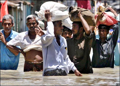 Bangladeshis carry supplies through floodwaters in Sirajganj when the River Jamuna burst its banks.(03/08/07)