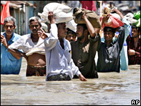 Bangladeshis carry relief supplies as they wade through floodwaters in Sirajgonj (3 August 2007)