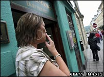 Woman smokes outside a pub in England