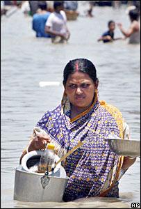 Woman wades through flood waters in Bangladesh