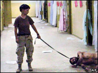 Lynndie England holding a leash attached to a detainee in late 2003 at the Abu Ghraib prison