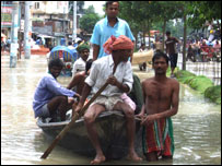 A man rows a boatful of people along a flooded street