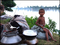 A young boy whose family abandoned his home sits by the riverbank
