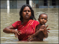A mother hold her child above the floodwaters in Bangladesh