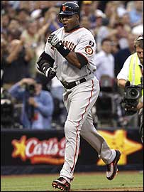 Barry Bonds celebrates as he rounds third base after hitting his record-equalling home run