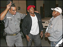 A police officers escorts Erislandy Lara (left)  and Guillermo Rigondeaux (right)
