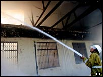 A fireman sprays water at a government building burned in a violent protest