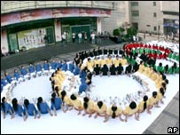 Staff members from a shopping centre pose in red, green, black, yellow and blue T-shirts to form the Olympic rings in Hangzhou, in China's eastern Zhejiang Province
