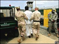 Un detenido es custodiado por dos guardias en Guantánamo.
