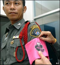 "A police officer wears a pink armband featuring 'Hello Kitty"" to show reporters"