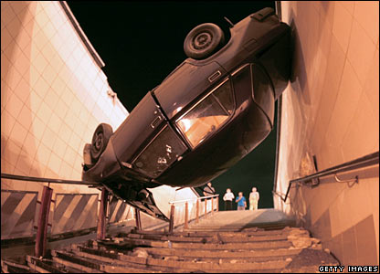 Car rests upside down against a wall in Moscow