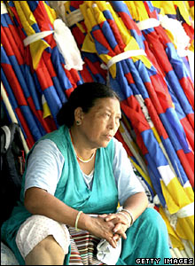 A Tibetan women beside a collection of Tibetan flags