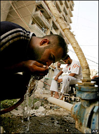 An Iraqi man drinks water from a hose in central Baghdad (4 August 2007)