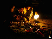 Iraqis eat dinner by the light of an oil lamp in Sadr City, Baghdad, during a blackout (4 August 2007)