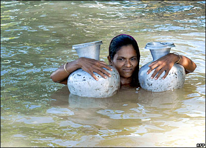 A villager carries metal pitchers jugs to fetch fresh water amid flooding in Dhaka, Bangladesh