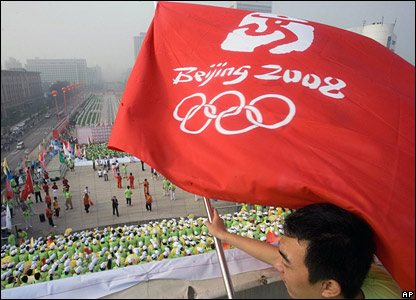 Chinese man waves  flag with Beijing Olympic Games logo