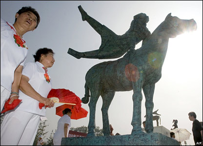 Chinese performers stand near a sculpture in Beijing