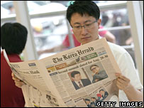 South Koreans read newspapers reporting on the upcoming summit