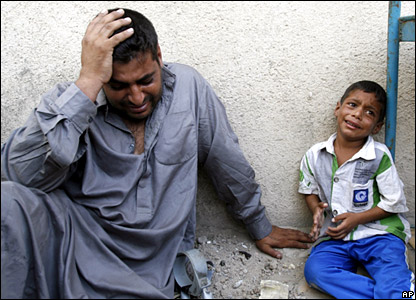Mustafa Hussein (right) grieves for his uncle and an older relative outside a hospital morgue in Sadr City