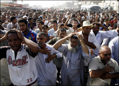 Mourners march in front of the coffins of the victims of the raid in Sadr City