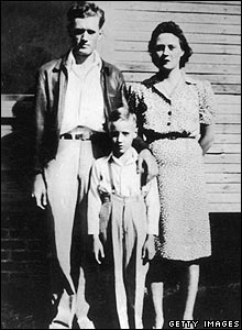 circa 1945:  Elvis Presley standing between his parents outside their home in Tupelo, Mississippi.