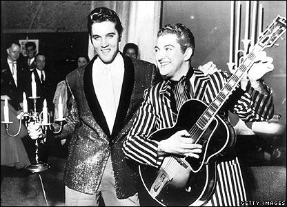 circa 1955: Elvis Presley and Liberace exchange personal trademarks while standing together. Presley holds a candelabra while Liberace plays guitar