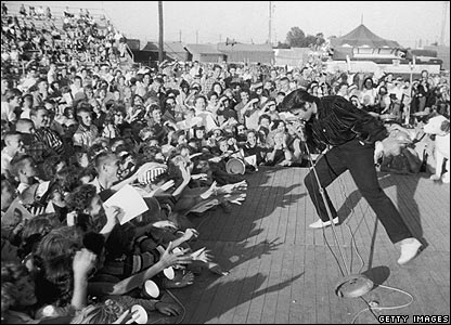 circa 1957:  Elvis Presley performing outdoors on a small stage to the adulation of a  young crowd.