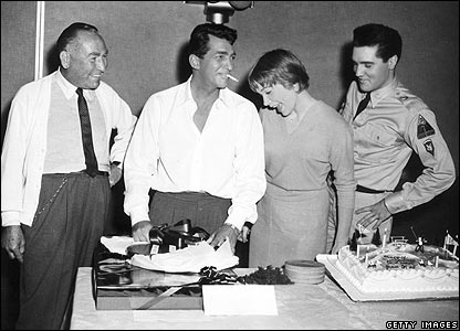 1961: Dean Martin (second left) celebrates his birthday with producer Hal Wallis (left), Shirley MacLaine and Elvis Presley while in production for Joseph Anthony's film All in a Night's Work.