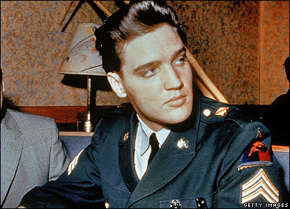 Circa 1958: Elvis Presley sits in a restaurant wearing his US Army uniform.