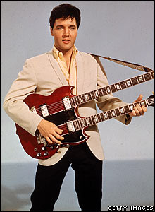 Portrait of Elvis Presley as he holds a double-necked guitar, mid 1950s.