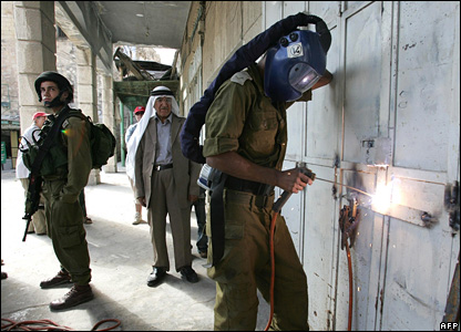 Hajj Jawdat Hassouneh looks on as an Israeli soldier welds shut his shop in the West Bank city of Hebron