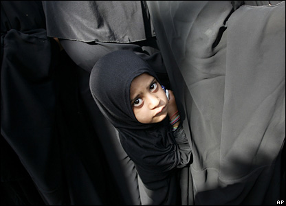 An Iraqi girl peeks out as women pilgrims line up at a security checkpoint leading to the shrine of Imam Moussa al-Kadhim in Baghdad