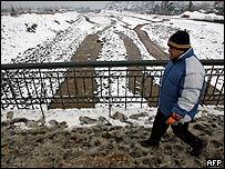 Un hombre camina sobre un puente sobre el helado río Mapuche en Santiago