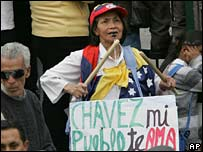"A woman in Quito with a banner reading ""Chavez, my town loves you"""