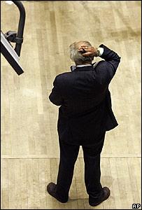 Un corredor de bolsa se agarra la cabeza en el mercado de acciones de Nueva York