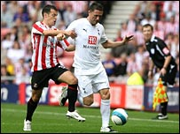 Robbie Keane takes on Ross Wallace