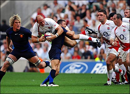 Lawrence Dallaglio is tackled by France scrum-half Pierre Mignoni