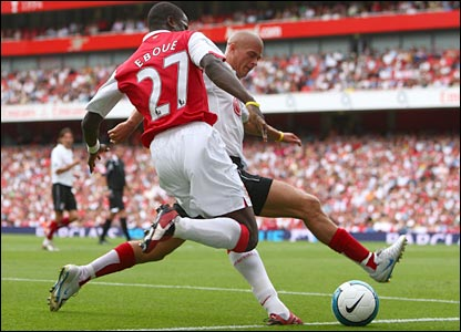 Emmanuel Eboue is challenged by Paul Konchesky