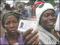 A Sierra Leone voter holds up her voter registration card a