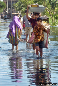 People carry possessions through floodwater (Getty Images)