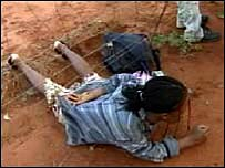 A Zimbabwean woman crawling under a border fence to South Africa