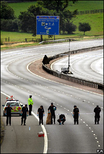 Police search the M40 after biker murder