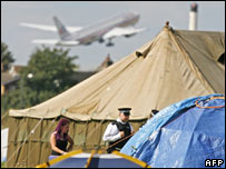 An aircraft takes off as protesters set up their camp 