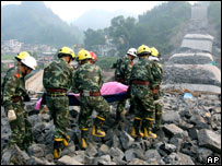Rescuers carry a victim at the site of a collapsed bridge in Fenghuang