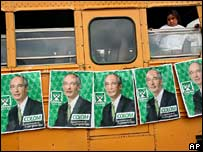 A girl peers out of a window of a bus plastered with election posters